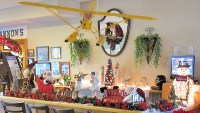 "A model Piper Cub is displayed about some of C.J. Cannon's festive holiday decorations. Located in the Vero Beach Airport terminal building, C.J. Cannon's advertises that ""the only thing we overlook is the runway."""