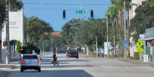 "Traveling westbound the ""Twin Pairs"" in downtown Vero Beach a vehicle brakes for pedestrians caught in the crosswalk when the traffic light turned green."