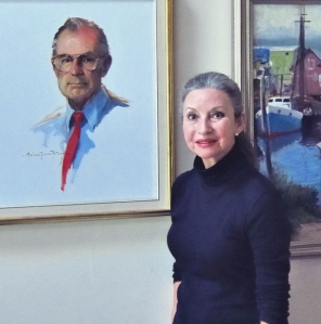 Marlene Putnam, an accomplished portraiture and seascape painter, poses in front of a portrait of her late husband, Herald Putnam.