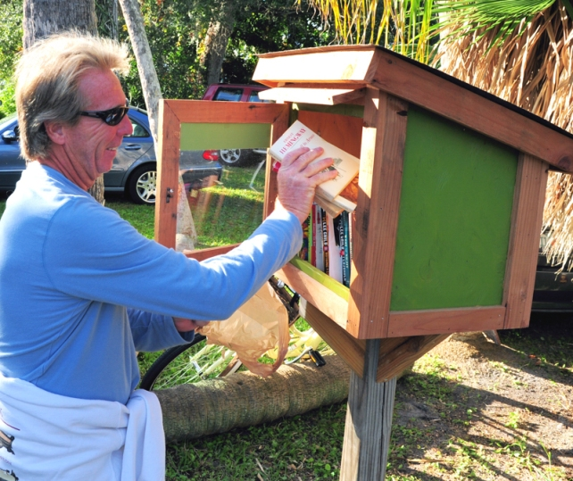"A resident of Old Riomar contributes  books to the ""Little Library"" in front of J.J. Wilson's home on Riomar Drive."