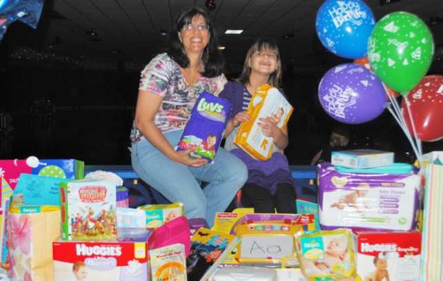 Lynn Mueller (left) and daughter Faith with the baby gifts donated by her friends to celebrate at Faith's 9 year old birthday party.