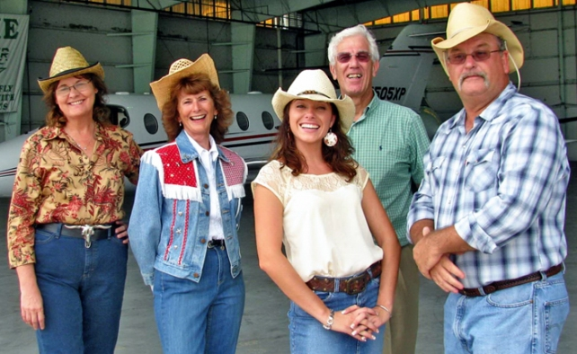 :  DE PLANE! DE PLANE! Habitat Cracker Hoedown Committee members check out the new event venue: the Sun Aviation Sun Jet Center. Robin Patton, Connie Poppell, Anna Valencia of Presenting Sponsor Girard Equipment, Inc., Andy Bowler and Chair David Taylor.