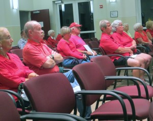 Small group of grim red shirted anti-Seven50 protestors at Sebastian City Council meeting.
