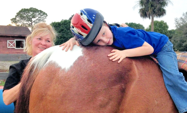 Cindy Devine, executive officer of the Florida Equestrian Foundation, with Vinny Henry, who is giving 19 year old Napolean a big hug.