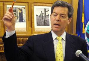 After four years of cutting taxes and state spending, Kansas Gov.Sam Brownback faces a revolt from within the Republican Party.  JOHN HANNA/AP