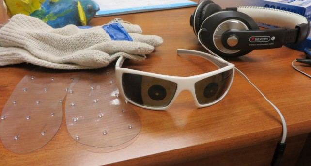 Partially obstructed glasses, gloves with fingers taped and headphones help simulate dementia.
